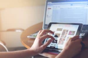 Woman holding iPad doing website edits